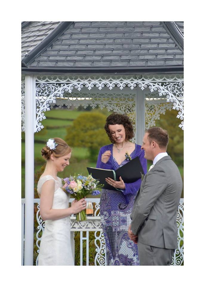 A bride and groom stand in front of a permanent gazebo smiling and laughing whilst their celebrant Keli Tomlin officiates their wedding ceremony. The wind is blowing. The bride is laughing.
