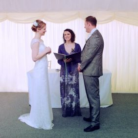 A Bride and Groom stand in front of their Celebrant Keli Tomlin and speak their vows