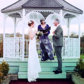 A bride and and groom stand beneath clear umbrellas on the first step of a wooden gazebo. Their Celebrant Keli Tomlin stands beside them officiating over their outdoor wedding ceremony
