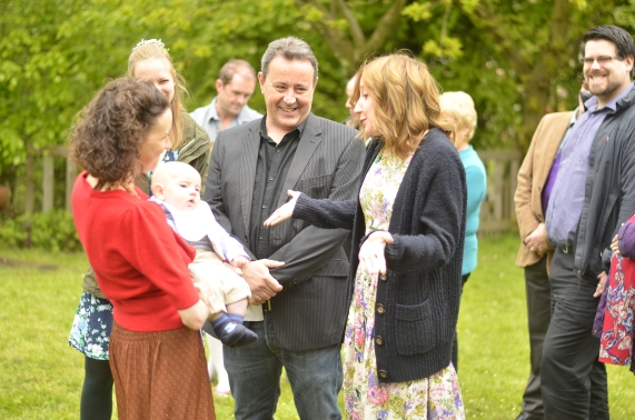 Family stand around as a Baby is celebrated during a Naming Ceremony. One man laughs and a woman holds her arms out smiling.