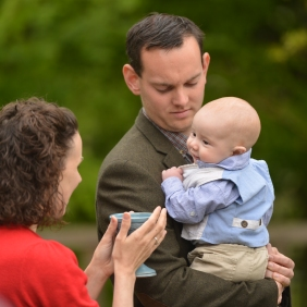 A baby, held by its father, is blessed with Water by Celebrant Keli Tomlin
