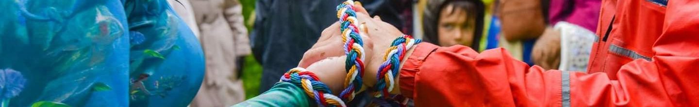 A couple have their hands bound together by a brightly coloured plaited cord as part of a Handfasting by Keli Tomlin Ceremonies