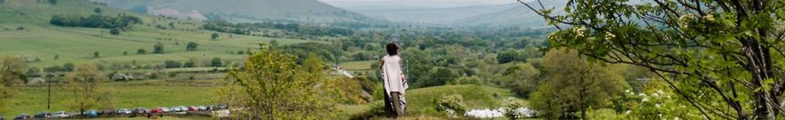 A woman stands with her back to the camera looking out a the Edale Valley