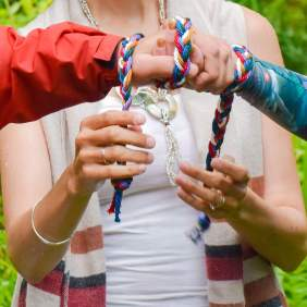 two hands being bound together with a rainbow coloured handfasting cord by Celebrant Keli Tomlin