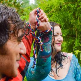a smiling couple hold up their bound hands in celebration of their handfasting by Keli Tomlin, Celebrant