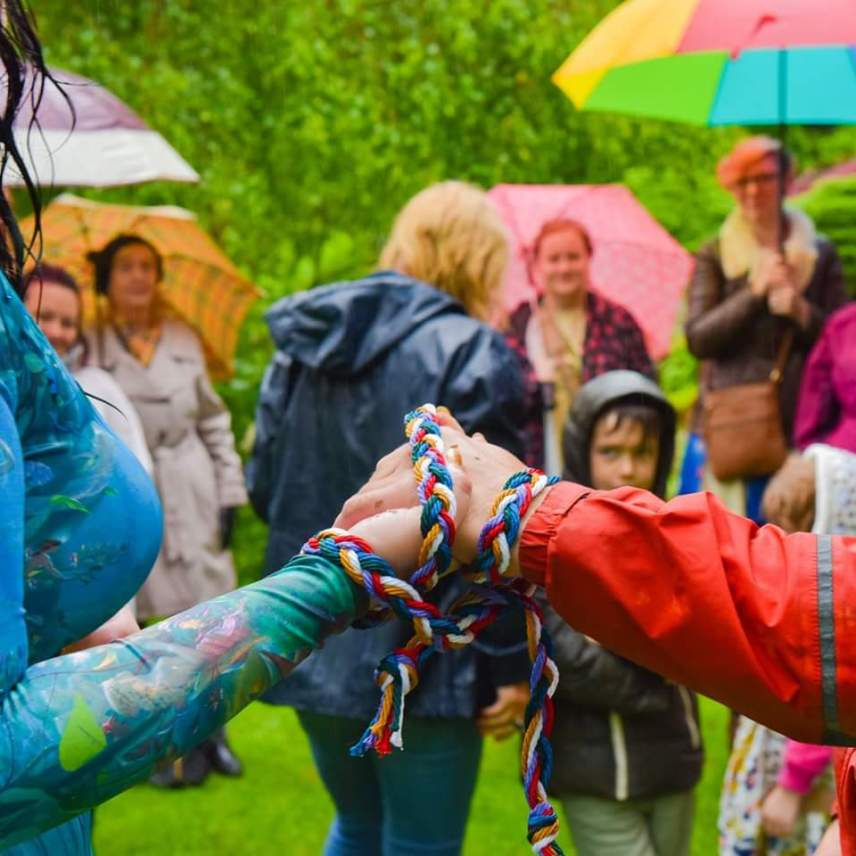 Guests stand watching couple during Handfasting in the rain
