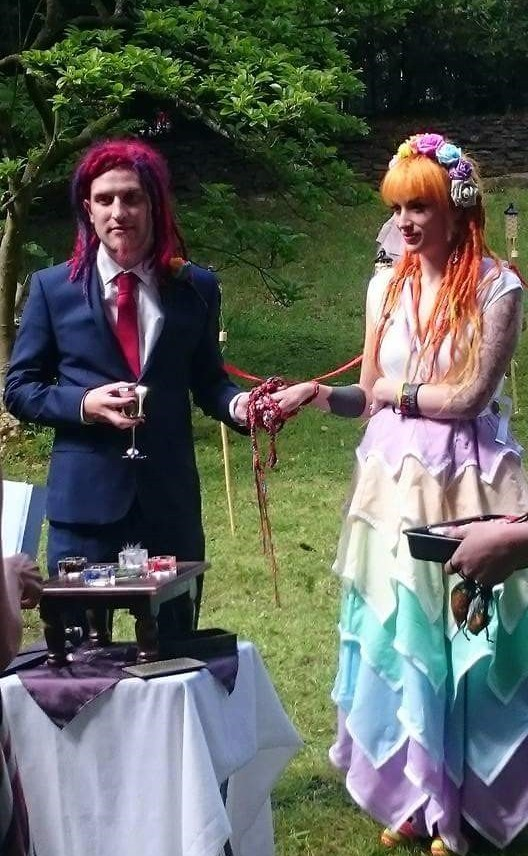 An Alternative Bride and Groom in rainbow colours stand together with their hands bound in Handfasting during their pagan wedding ceremony