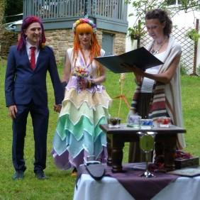 An alternative bride and groom, wearing rainbow colours, stand beside their Celebrant Kei Tomlin who reads from their Pagan Wedding Ceremony