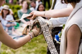 Hands are bound in handfasting by a black and white belt. Part of a four part handfasting by Keli Tomlin Ceremonies