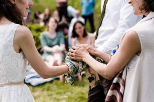 a bride and groom stand with their hands bound together by many different handfasting cords. The Celebrant Keli Tomlin stands with her hands on top of theirs in blessing
