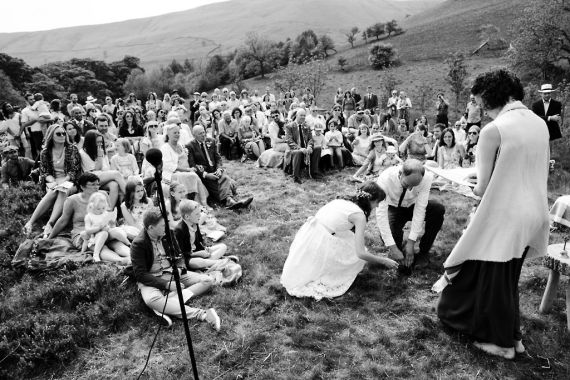A bride and groom plant a tree as their guests look on, Celebrant Keli Tomlin is watching. The image is in black and white.