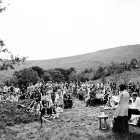 The guests are gathered on the grass watching the Celebrant Keli Tomlin deliver the wedding ceremony. The image is black and white