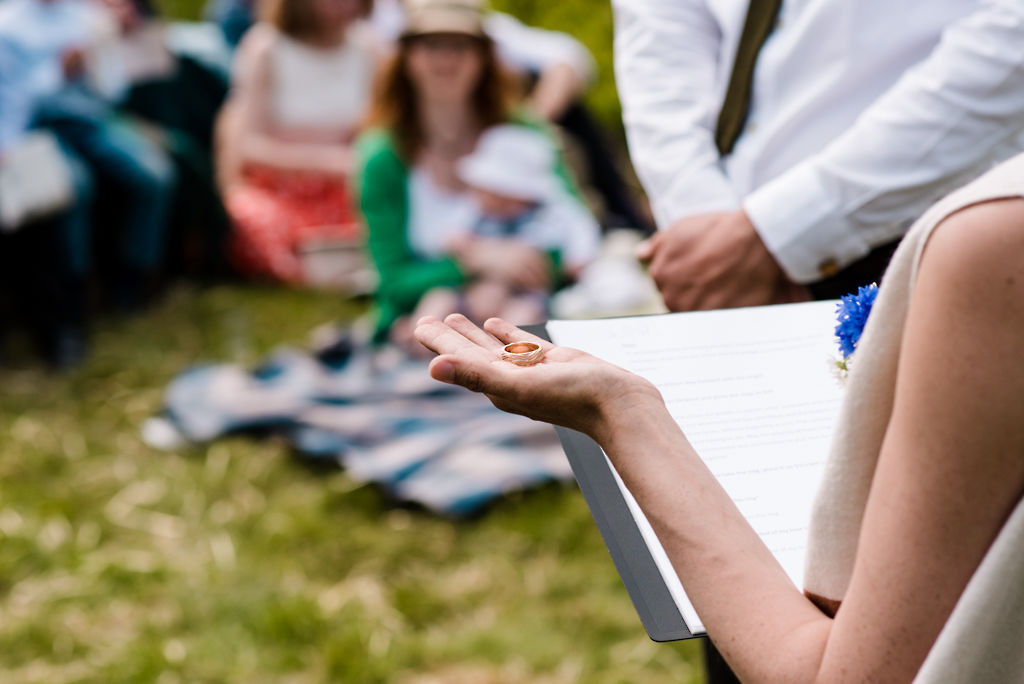 Celebrant Keli Tomlin holds a wedding ring in her hand during an outdoor ceremony