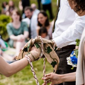 Two handfasting cords tied over two hands, one braided cords and the other a strip of hessian with crocheted ivy leaves. Being tied by Celebrant Keli Tomlin