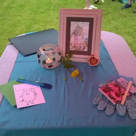 A Baby Naming altar including a photograph, a candle in a glass holder, gardening gloves, paper and pen and yellow flowers