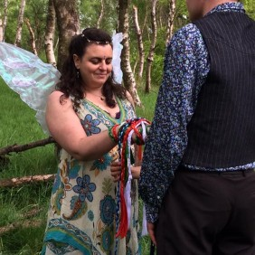 A Fairy Bride wearing wings and a white and green dress stands with her eyes closed smiling. Her hand is tied to her husbands with colourful handfasting cords by Celebrant Keli Tomlin