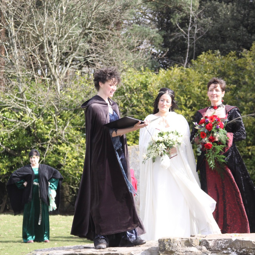 Pagan Celebrant Keli Tomlin officiates over the wedding of two brides in medieval dress in the Stone Circle at Ruthin Castle.