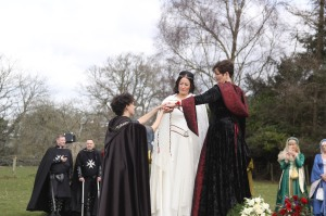 Two Brides dressed in medieval clothes stand beside Pagan Celebrant Keli Tomlin as she performs a Handfasting for them