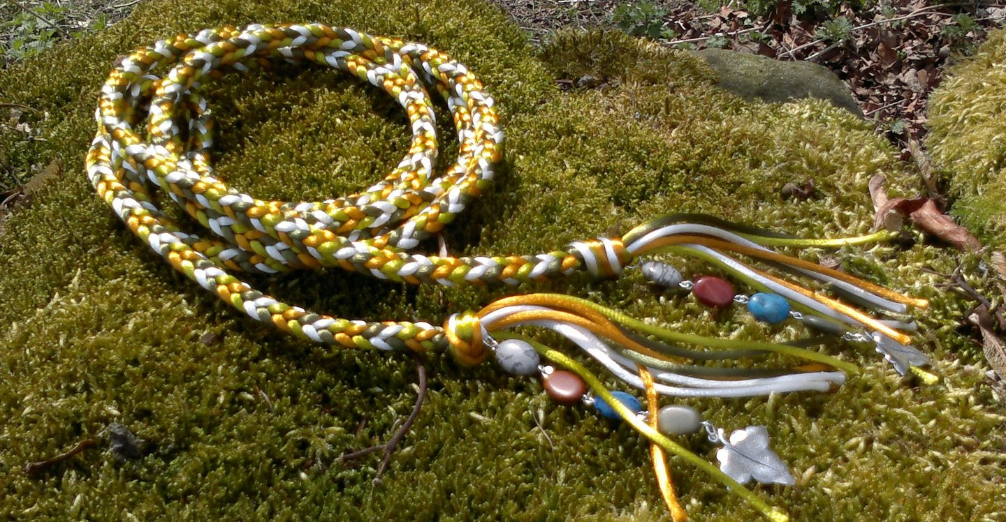 a handfasting cord made from gold, white and green cords lies curcled on a patch of moss. Semi-precious stones and silver ivy pendants are attached to each end.