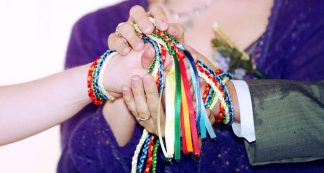 a couples hands are bound together with rainbow coloured handfasting cords. The Celebrant, Keli Tomlin, holds these joined hands between her own.