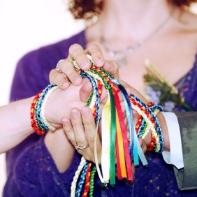 Hands bound together with rainbow handfasting cords during a ceremony by Keli Tomlin