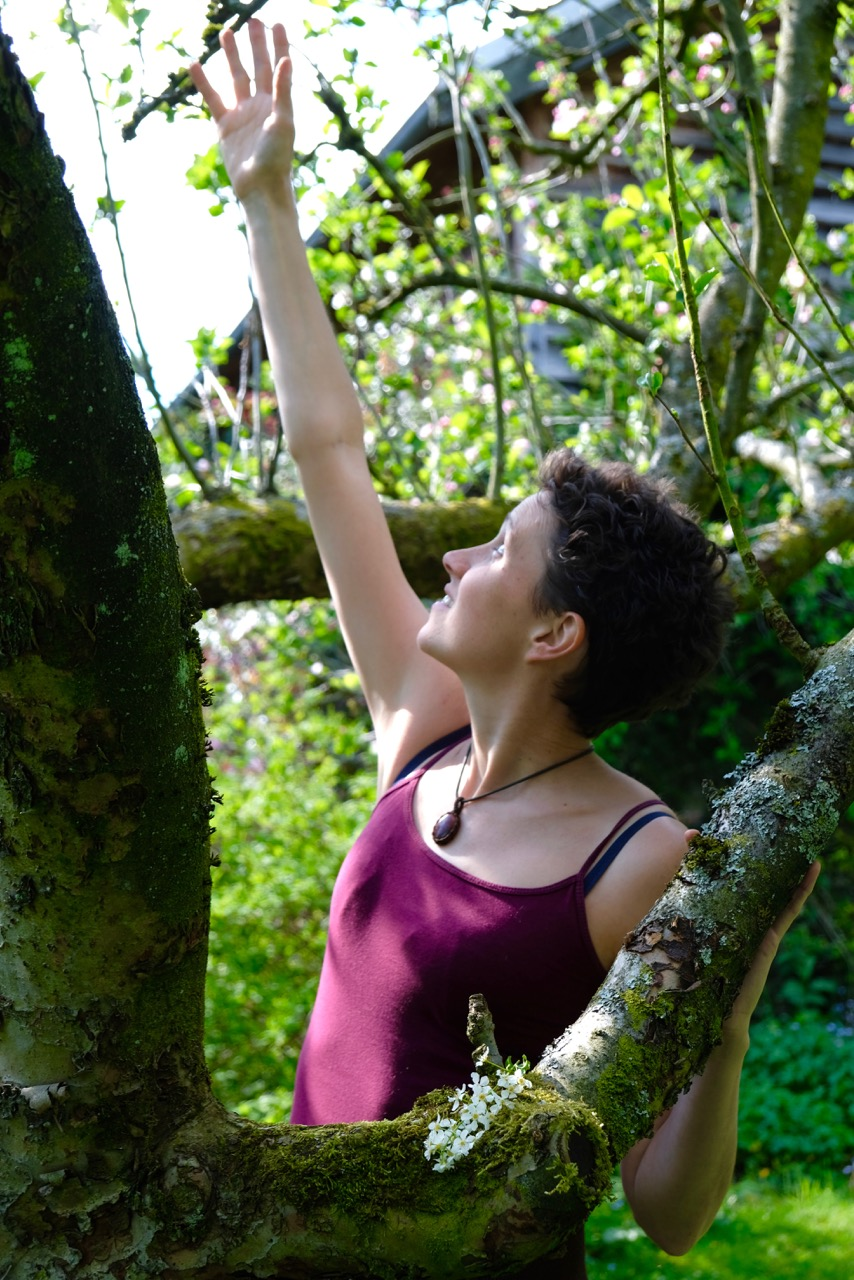 A woman stands beside the branches of a tree and reaches up with one hand towards the sky