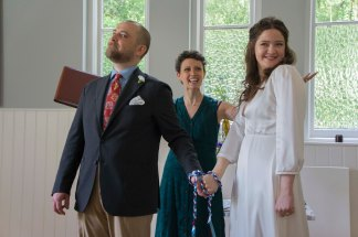 A Bride and Groom have their hands tied as part of a handfasting ritual. They are smiling at their guests. The Celebrant Keli Tomlin stands behind them smiling, her arms spread to present them to the guests.