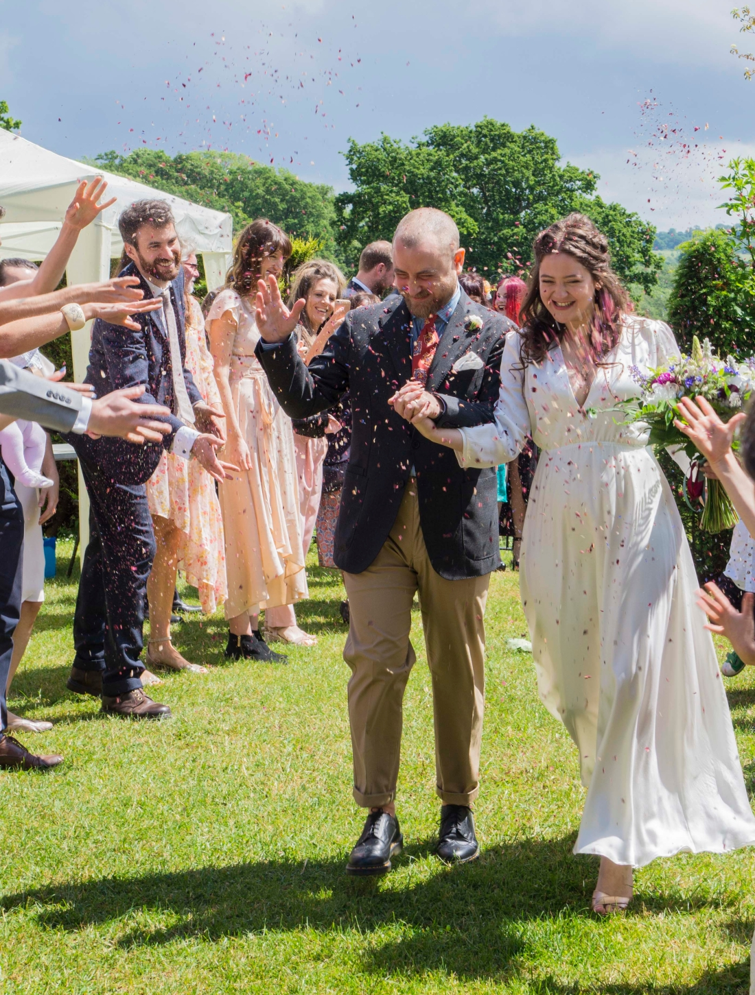 The Bride and Groom walk amongst their guests in a cloud of confetti, they are laughing