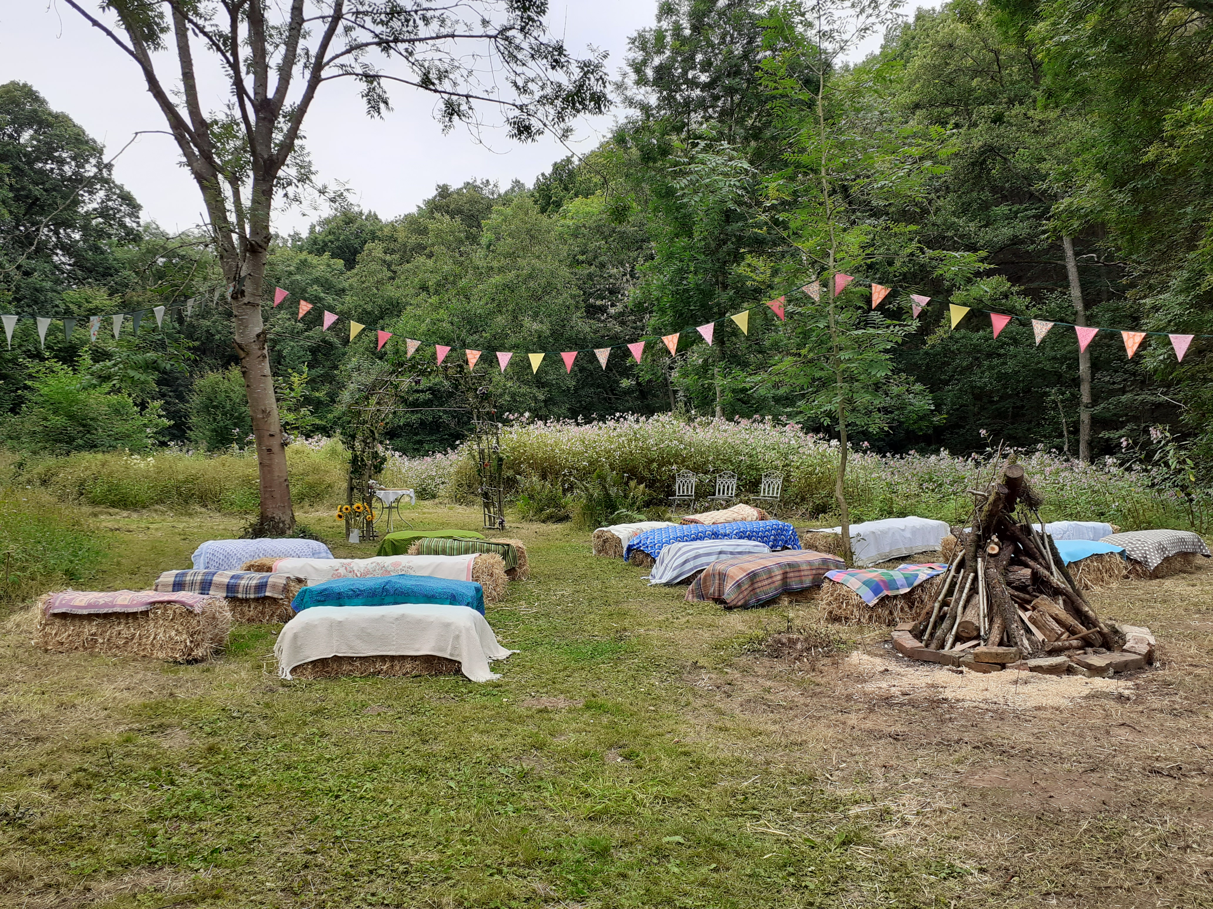 A garden decorated for an outdoor wedding ceremony with covered haybales, bunting and an unlit bonfire