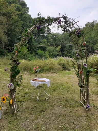 A DIY flower arch for an outdoor garden wedding. Beside it is a bucket of sunflowers and behind is an altar table with a Handfasting cord and vase of flowers. Taken by Keli Tomlin