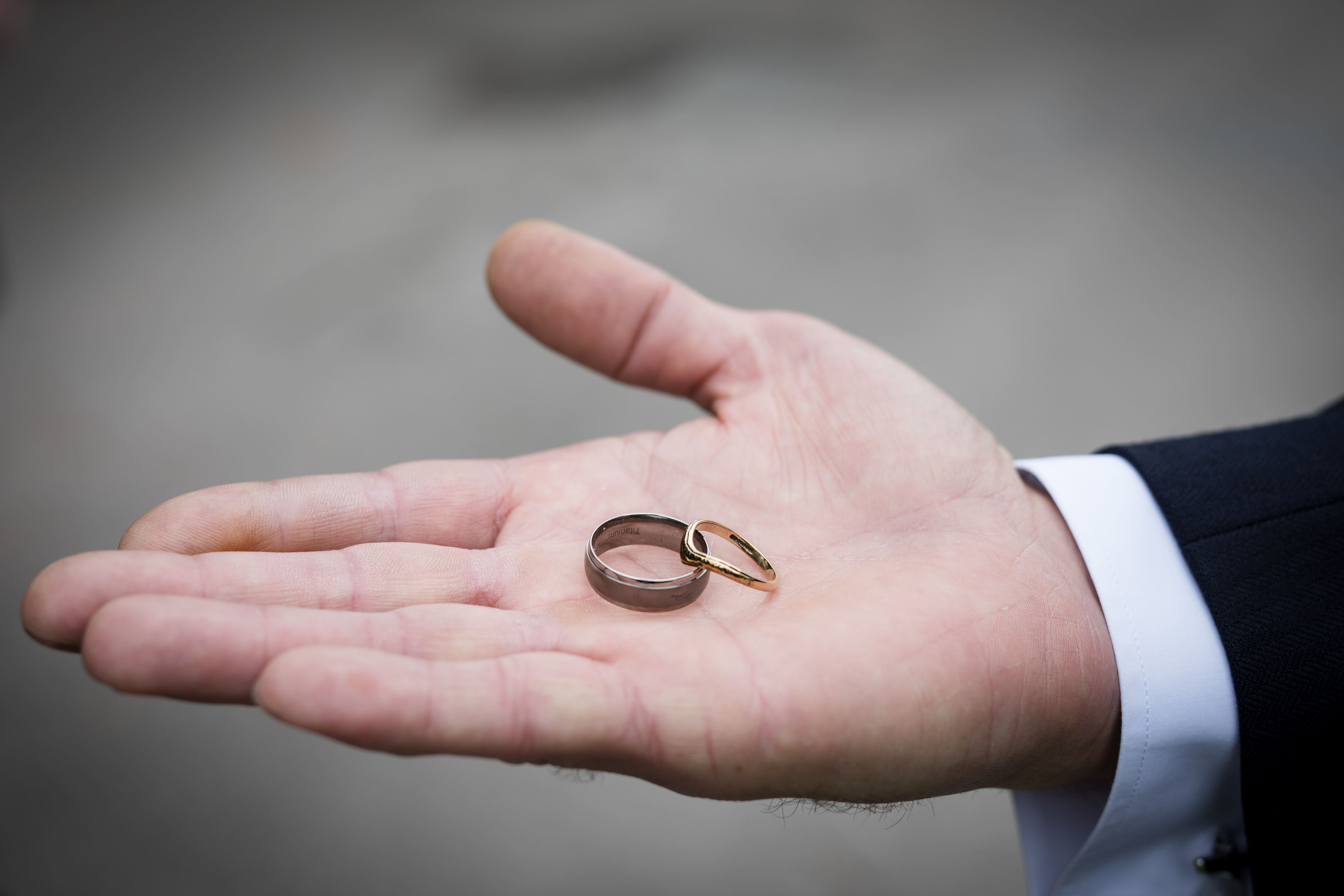 Two wedding rings, one silver and wide, one gold and thin, sit on the palm of a man's hand.