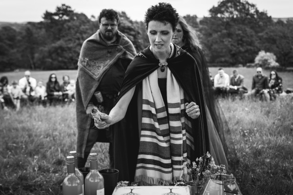 Pagan Celebrant Keli Tomlin uses a sage bundle to smudge the wedding altar while the bride and groom stand behind and watch