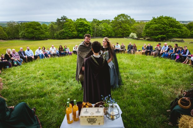 A Viing Bride and Groom stand at the centre of a circle of friends and family during their wedding ceremony led by Celebrant Keli Tomlin. There is an altar in the foreground with a wooden box, candles, forget-me-nots, bottles of mead and cake.