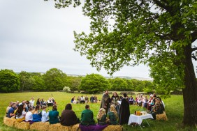 A Pagan Viking Wedding is conducted beneath the branches of an overhanging Oak tree. Bride, Groom and Celebrant Keli Tomlin are dressed in Viking attire at the centre. Guests sit on hay bales in a circle around them