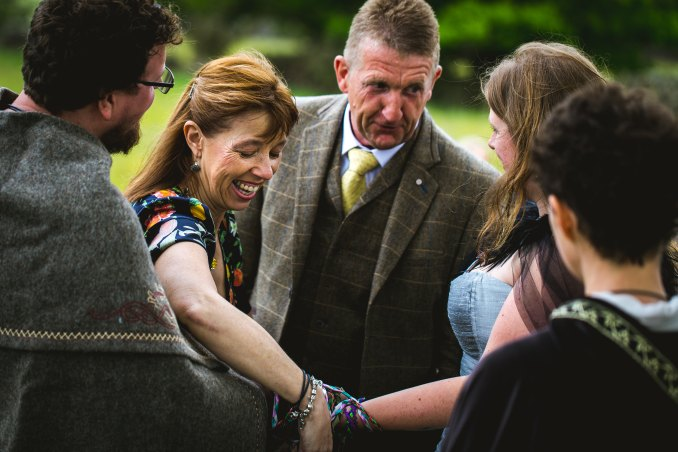 A viking bride and groom have their hands bound together with blue and purple robbons as part of a handfasting lead by Celebrant Keli Tomlin. Everyone is smiling.