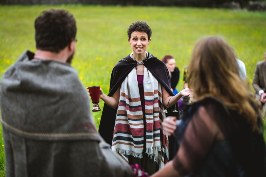 A Celebrant smiles at the bride and groom during the cake and wine ritual of a pagan viking wedding in Grindleford by Keli Tomlin Ceremonies