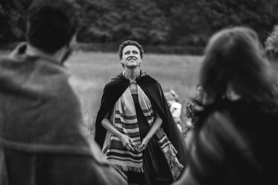 A Pagan Celebrant (Keli Tomlin) stands looking at the sky, smiling, as the outdoor wedding ceremony comes to a close. The image is black and white.