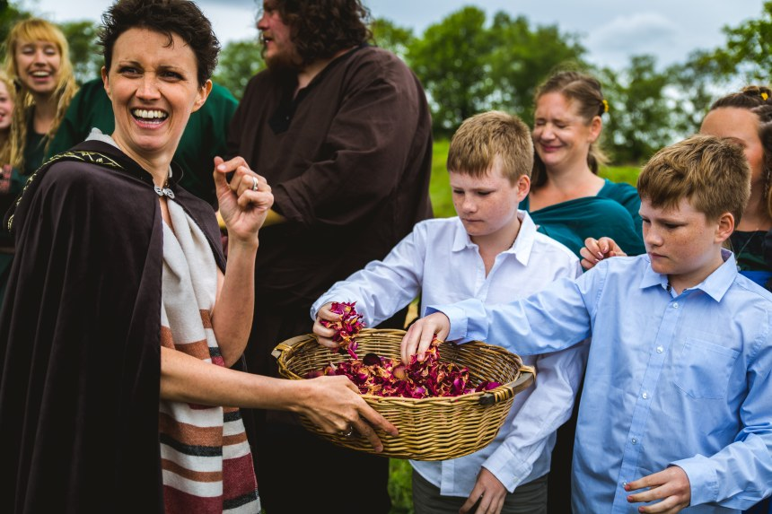 Keli Tomlin Celebrant at a Viking Wedding Ceremony hands dried pink rose petal confetti to two young boys. She is looking over her shoulder and smiling broadly