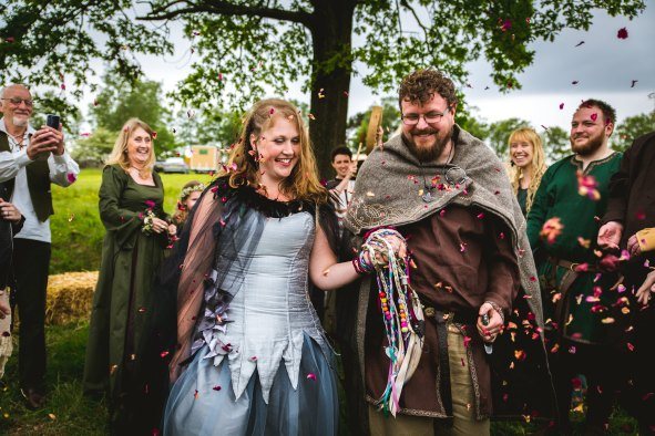 a viking bride and groom walk through their guests who throw confetti. theire hands are tied with handfasting cords and their Celebrant Keli Tomlin drums in the background to signal the end of their outdoor wedding ceremony