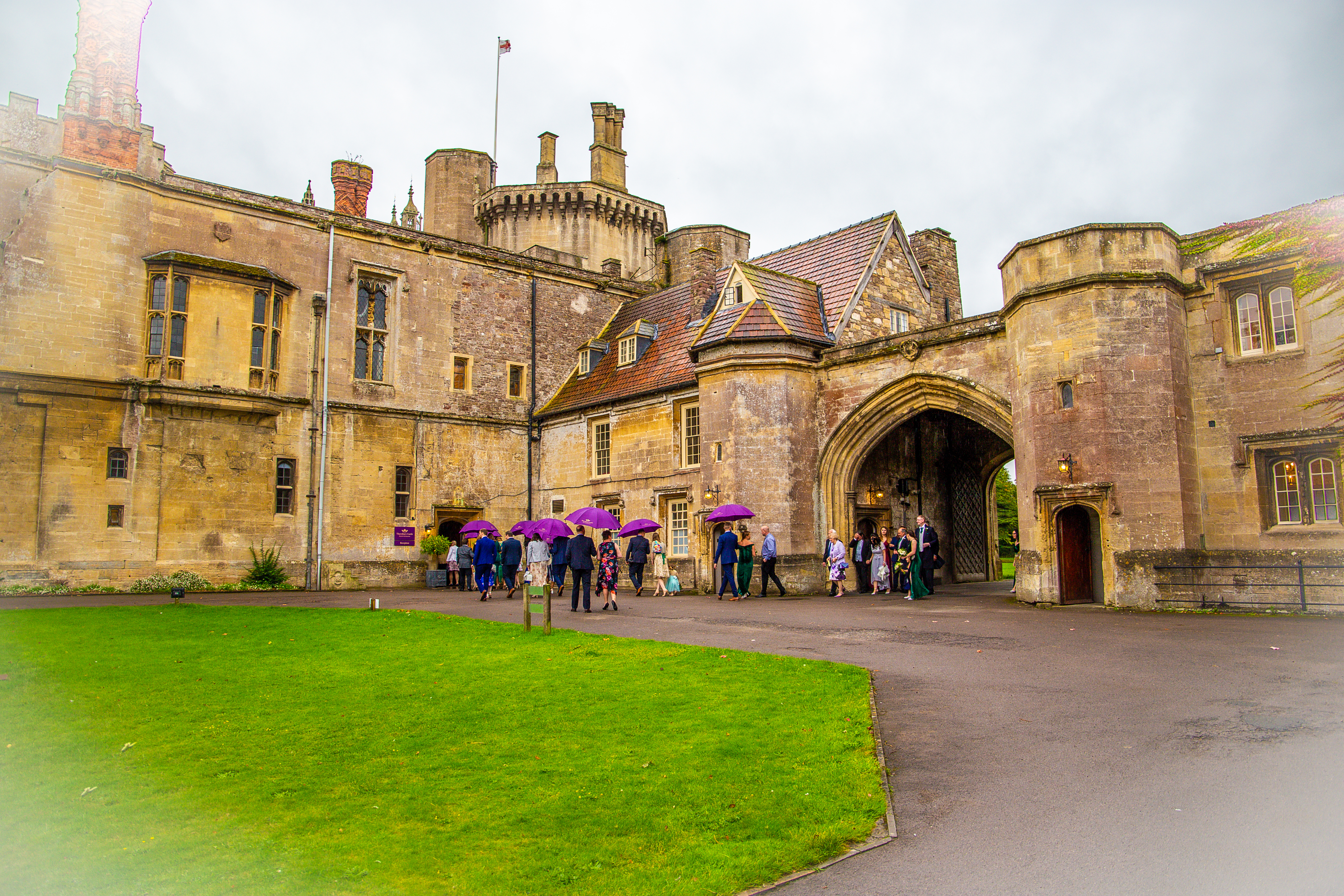 The Outside of Thornbury Castle, a yellow stone building with turrets and an archway, with a lawn in front. Wedding guests move towards the entrance carrying purple umberellas