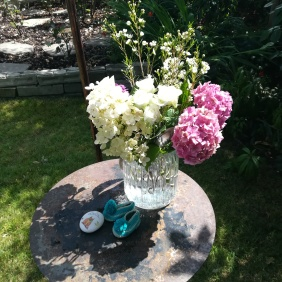 An altar set for a Naming Day Ceremony led by Keli Tomlin including a vase of hydrangea, two small baby shoes and a pebble painted with a cat.