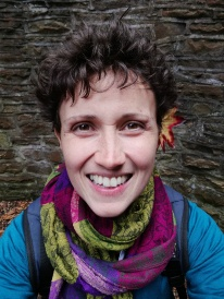 A woman (Keli Tomlin) smile broadly at the camera, there is a brightly coloured leaf tucked behind her ear.
