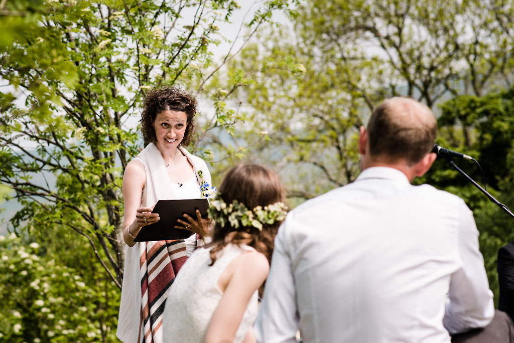 Celebrant Keli Tomlin smiles over at the bride and groom as she officiates over their outdoor wedding ceremony