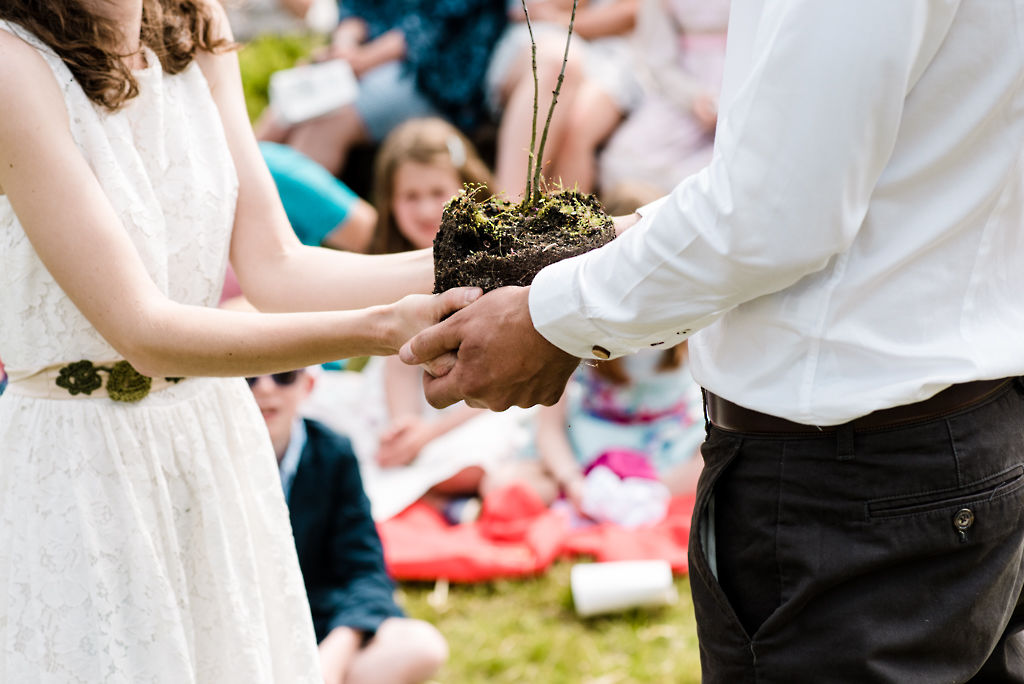 A bride and groom hold hands around an oak sapling which they are about to plant in the ground as part of their outdoor DIY wedding ceremony with Keli Tomlin Ceremonies