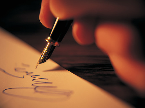 the tip of a fountain pen hovers above a page where a looping signature has been made in blue ink