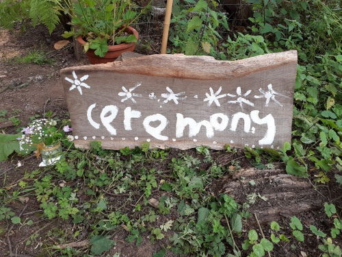 A large strip of wood with the word 'Ceremony' painted on in a childish hand in white paint. Beside it is a small jar of flowers. The sign leads to a DIY wedding by Keli Tomlin Ceremonies