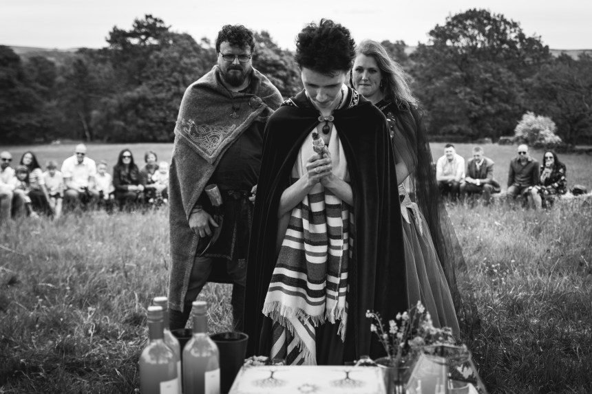 A Pagan Celebrant Keli Tomlin stands in front of an altar table, hands clasped in prayer. Behond her the bride and groom, in Viking dress, watch quietly. Behind them the guests sit in a circle. The wedding party is gathered in a meadow in Grindleford. The image is black and white.