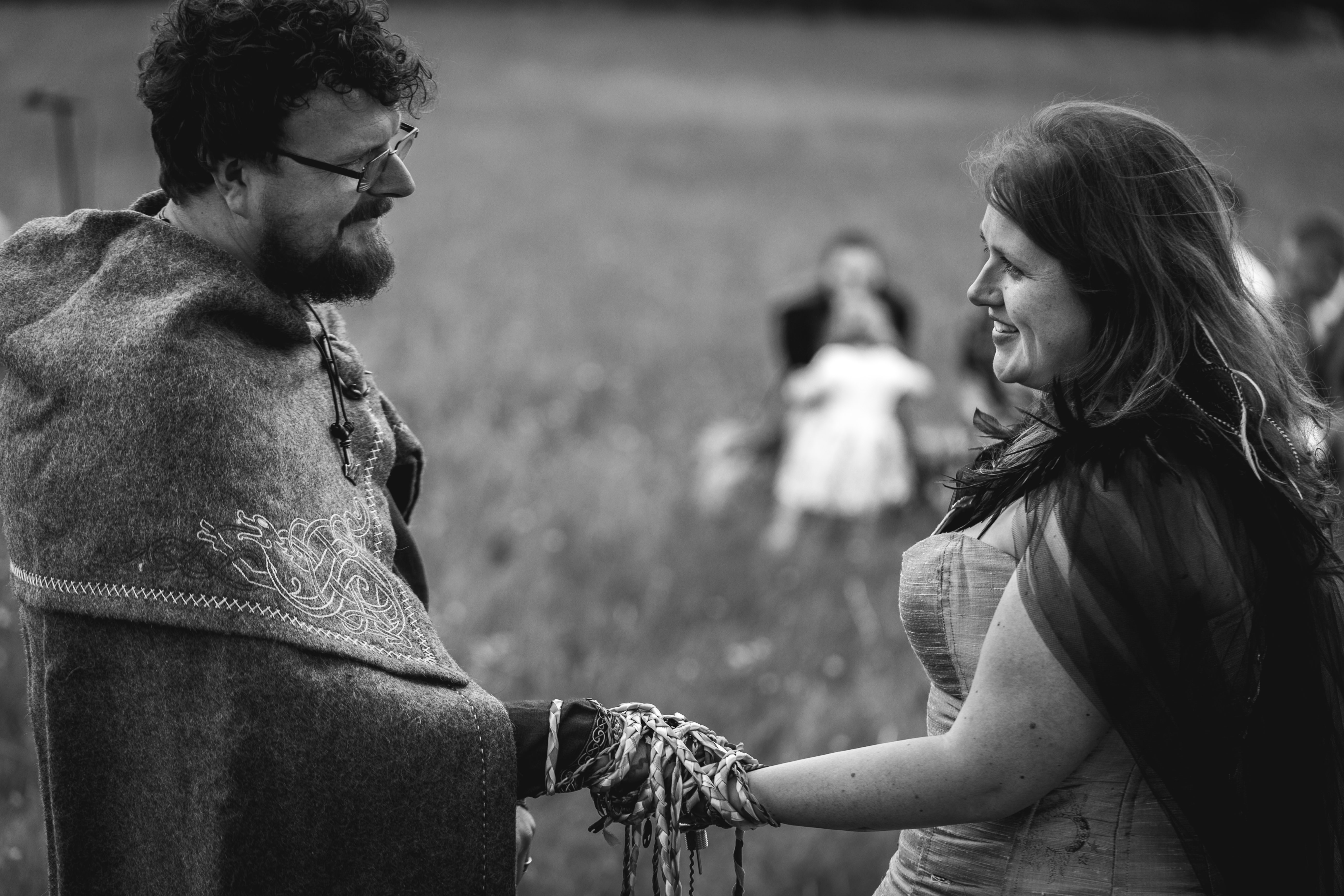Bride and Groom in Viking clothes stand together and smile at one another. Their hands are bound with Handfasting cords by Keli Tomlin. The image is in black and white.