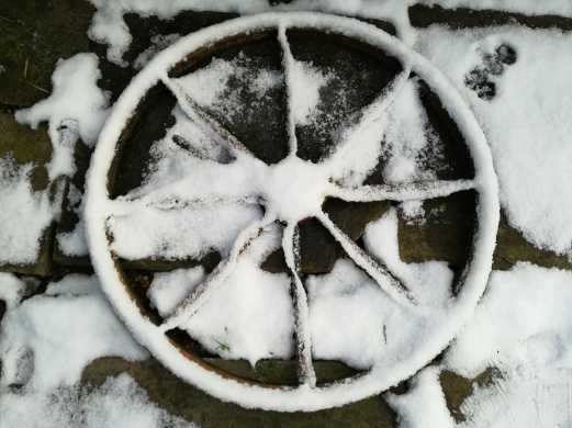 A wooden wheel laid on the ground covered in snow