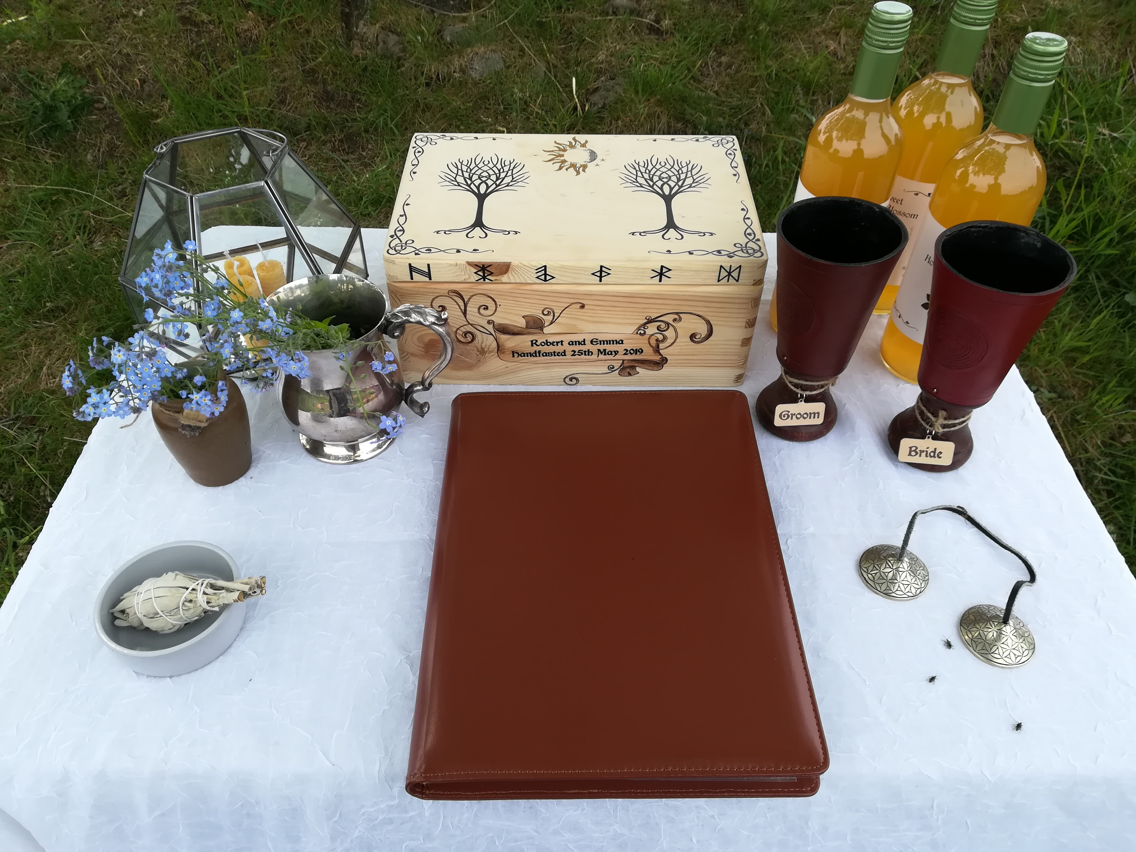 An altar set for a Viing Pagan Wedding by Celebrant Keli Tomlin including sacred bells, cups, mead, candles, forget-me-nots, sage smudge and a decorative wooden box.